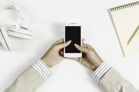 Top view of businesswoman hand with smartphone over white table Foto de archivo