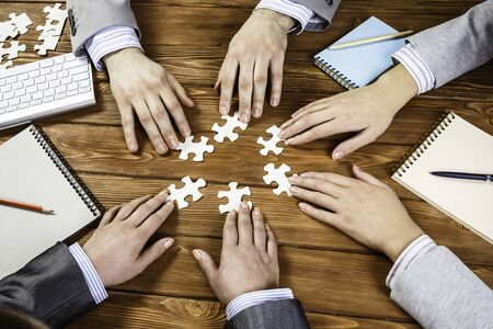 Group of business people sitting at table and assembling jigsaw puzzle Stok Fotoğraf