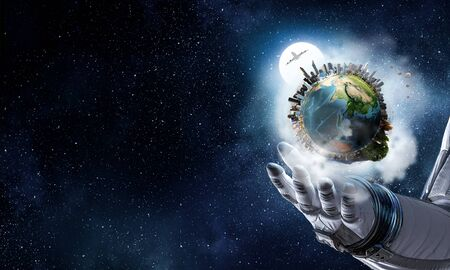 Astronaut hand and Earth in space.