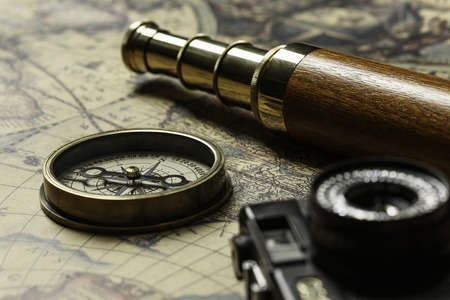 Concept of travel and discovery with old map and compass on it