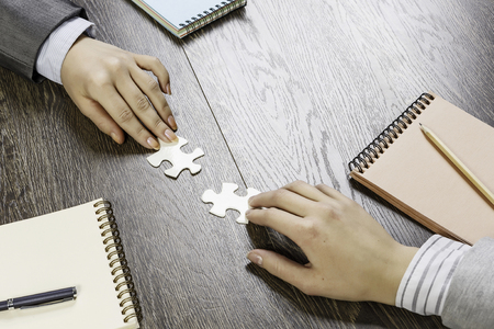 Hand of businesswomen completing puzzle with missing piece