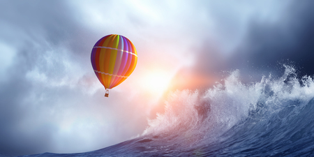 Color aerostat flying above stormy sea waves