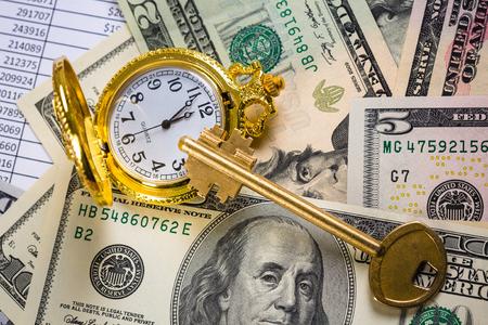미국 달러 지폐 위에 황금 열쇠와 주머니 시계
