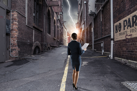 Businesswoman standing with back on city side street. Mixed media