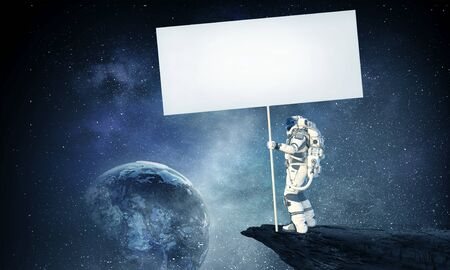 Astronaut holding blank banner for advertise. Elements of this image are furnished by NASA