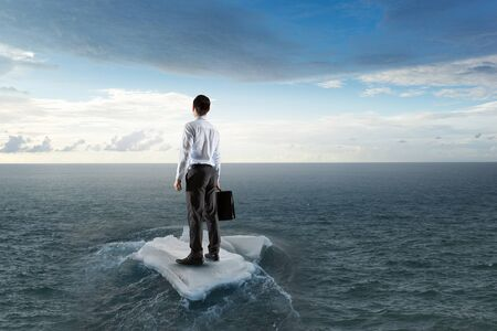 Businessman on ice block floating in sea . Mixed media Stock Photo