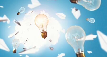 Glass light bulbs and paper planes flying around Stockfoto