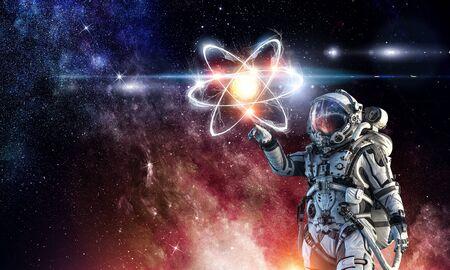 Astronaut in suit touching atom molecule. Mixed media