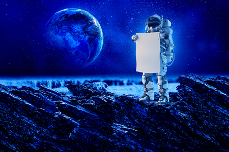 Astronaut in space holding white blank board.