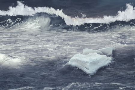Ice block floating on stormy sea waves. Mixed media