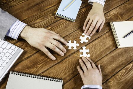 Group of business people sitting at table and assembling jigsaw puzzle Reklamní fotografie