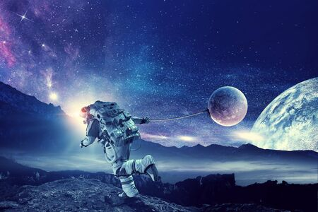 Astronaut in outer space pulling planet on rope.