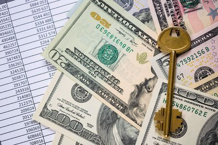 Golden key on top of US dollar bills Imagens