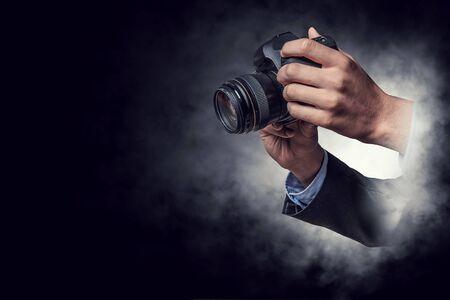 Close of businessman holding photo camera. Mixed media