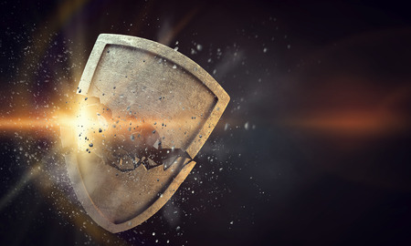 Cracked stone shield as symbol of security break. Mixed media