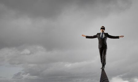 Businessman with blindfolder on eyes walking on rope high in sky