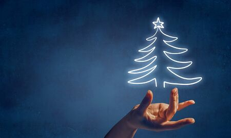 Close up of female hand taking christmas tree Stock Photo