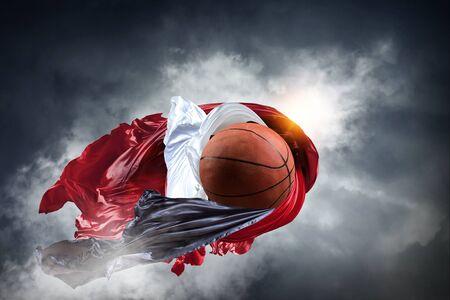 バスケットボールボールと空の背景に異なる色の生地。混合メディア 写真素材