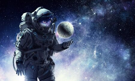 Astronaut holding Earth planet in palm. Stock Photo