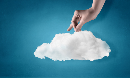 Man hand on blue background taking white cloud