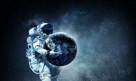 Astronaut carrying Earth planet in hands. Banco de Imagens - 94923984