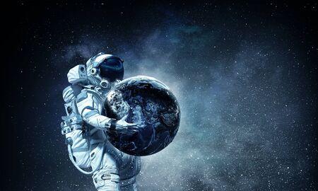 Astronaut die aardeplaneet in handen draagt. Stockfoto