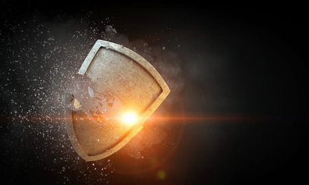Conceptual image with old stone broken shield. Mixed media 版權商用圖片
