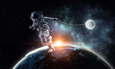 Astronaut in outer space pulling planet