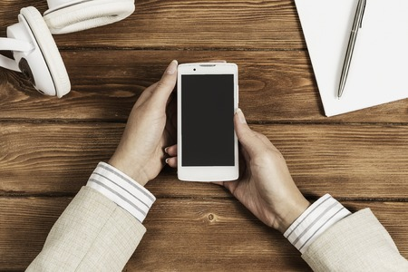Top view of businesswoman hand with smartphone over brown wooden table Standard-Bild