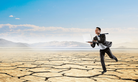 Businessman in suit with laptop in hands running in desert