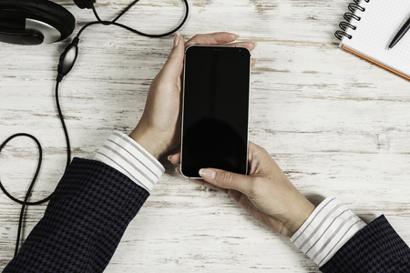 Top view of businesswoman hand with smartphone over white wooden table
