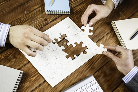 Group of business people sitting at table and assembling jigsaw puzzle Stock Photo