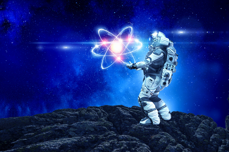 Astronaut in suit touching atom molecule. Mixed media