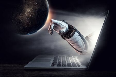 Hand of astronaut coming out of laptop screen. Standard-Bild