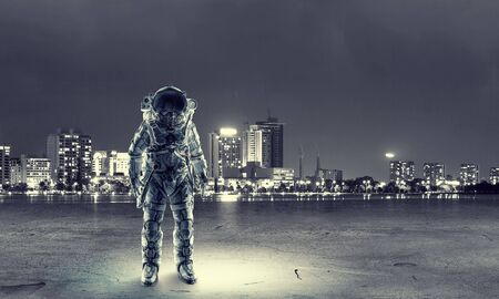 Spaceman in suit on cityscape background. Mixed media