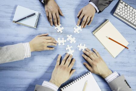 Group of business people sitting at table and assembling jigsaw puzzle Standard-Bild