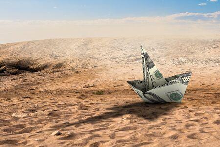 Dollar banknote ship in desert as symbol for financial crisis . Mixed media Фото со стока