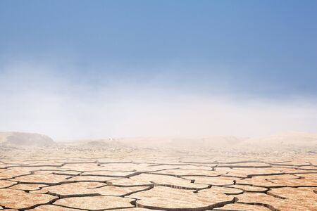 Cracked desert background with blue sky and mountains