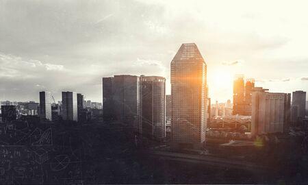 Modern grunge cityscape and sun rising. Mixed media