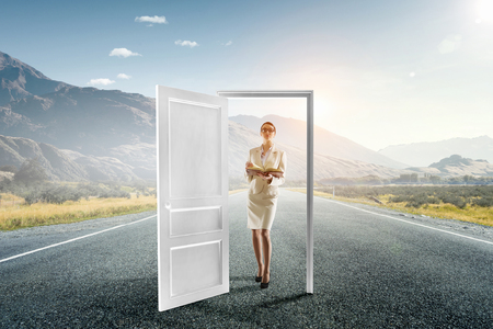 Elegant business lady outdoor and opened door. Mixed media Stock Photo