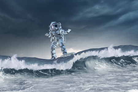 Spaceman on flying board surfing the sea. Mixed media