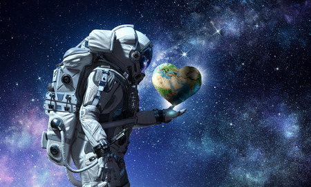 Astronaut holding Earth planet in palm. Stok Fotoğraf