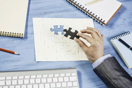 Hand of businesswoman sitting at table and assembling jigsaw puzzle Standard-Bild - 96298041