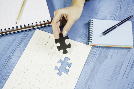 Hand of woman completing puzzle with missing piece