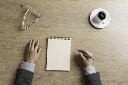Top view of businesswoman sitting at table and making notes in to notepad