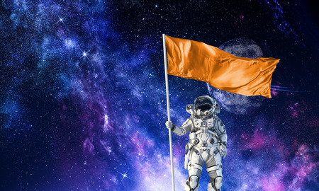 Astronaut man with flag in hand. Mixed media Stock Photo