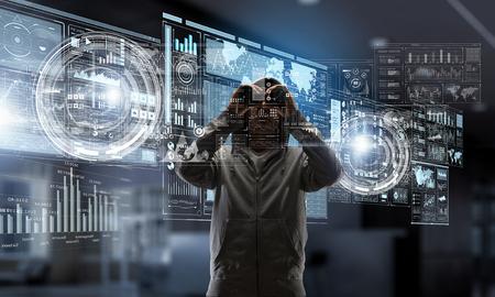 Unrecognizable man wearing hoody looking in to binoculars. Mixed media 스톡 콘텐츠
