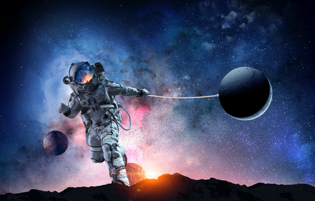 Fantasy image with spaceman catch planet. Mixed media 스톡 콘텐츠