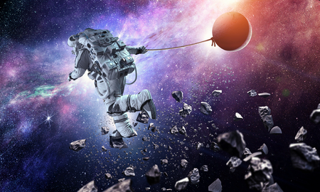 Astronaut in outer space pulling planet on rope