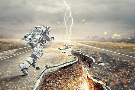 Astronaut in space suit running on cracked asphalt road. Mixed media